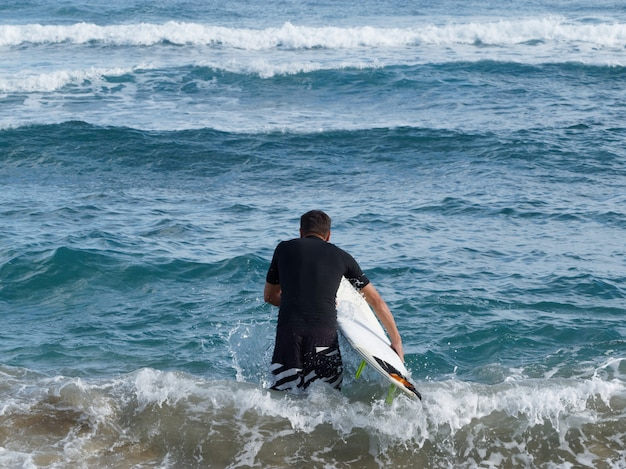 サーフボードで水に行く水着の男性。背面図。熱帯気候。