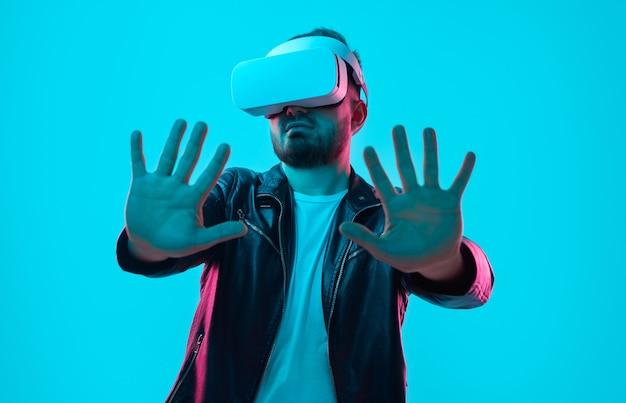 Мужчина в гарнитуре vr взаимодействует с виртуальной реальностью с протянутыми руками в студии с неоновыми огнями на синем фоне