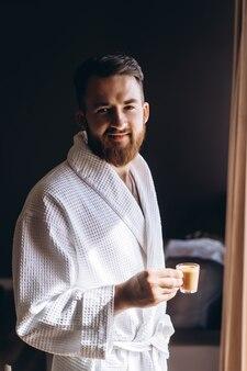 手にコーヒーのマグカップと白いバスローブの男性。