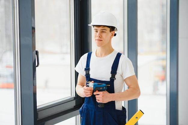 Рабочий-строитель мужского пола при установке окон на строительной площадке