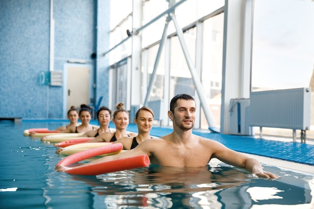 男性インストラクターと女性スイマーグループ、プールでのアクアビクストレーニング。水中の男性と女性、スポーツ水泳フィットネストレーニング