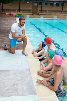 수영장에서 수석 수영을 돕는 남성 강사