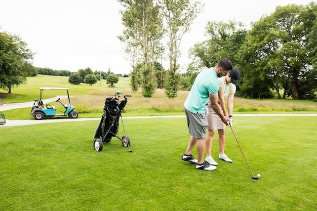 골프 학습에 여자를 돕고 남성 강사