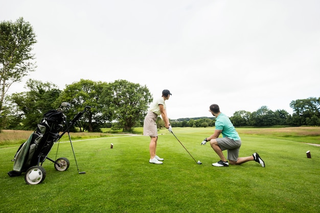 Male instructor assisting woman in learning golf