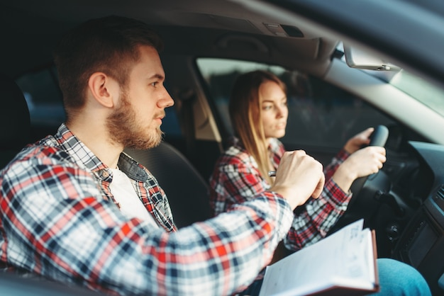 Male instructor and female student, driving lesson