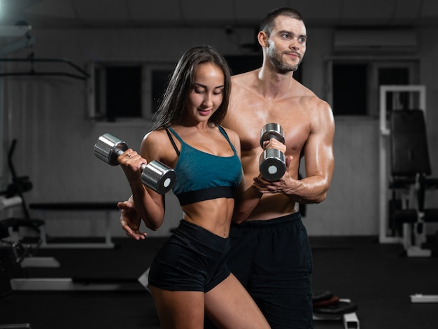 Male instructor and female train, lifting dumbbells