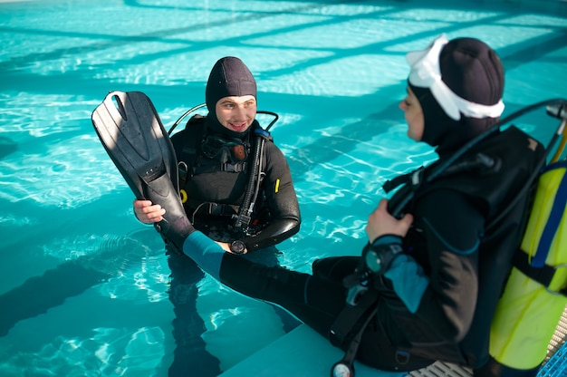 Male instructor helps woman to put on fins, diving