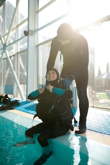Male instructor helps woman to set up scuba gear