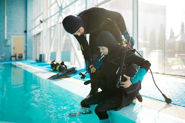 Инструктор-мужчина помогает женщине настроить акваланг