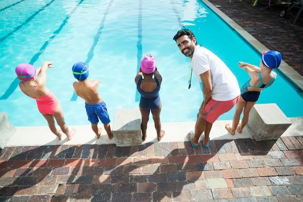 小さな水泳選手がプールに飛び込む準備をしている男性インストラクター