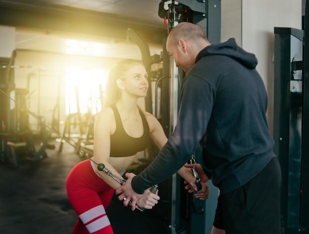Инструктор-мужчина тренирует блондинку, делая упражнения в кроссоверах в кроссовере в тренажерном зале