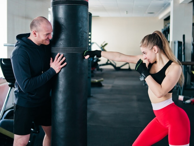 Male instructor trains young woman to do hand punches at punching bag in the gym