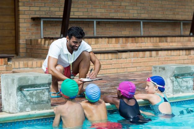 プールサイドで小さな水泳選手を説明しながらクリップボードに書く男性インストラクター