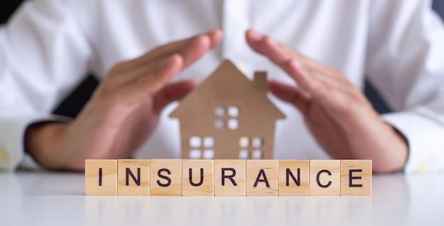 男性の保険代理店は家を守るために手を使っています。住宅保険または住宅保険の概念