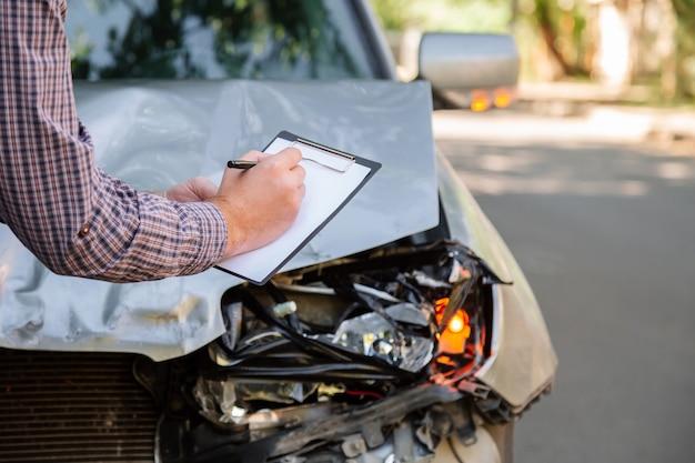 Мужской страховой агент с бланком автострахования против разрушенного автомобиля в автокатастрофе на дороге. разбила сломанную переднюю фару в автомобильной аварии. автострахование жизни и здоровья.