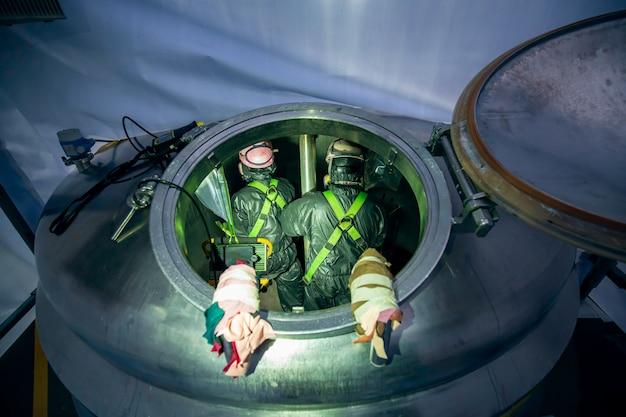男性の作業検査プロセス化学カラーペイントを石油貯蔵タンクの限られたスペースに