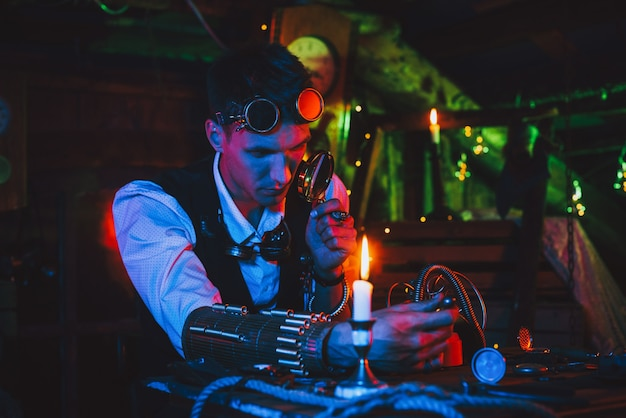 Изобретатель-мужчина в костюме стимпанк ремонтирует фантастический механизм за столом