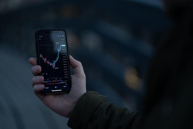 Инвестор-мужчина, использующий приложение для торговли акциями на смартфоне, трейдер анализирует динамику на графике форекс и поток цен на экране, стоя на открытом воздухе. селективный фокус на руке, держащей мобильный телефон