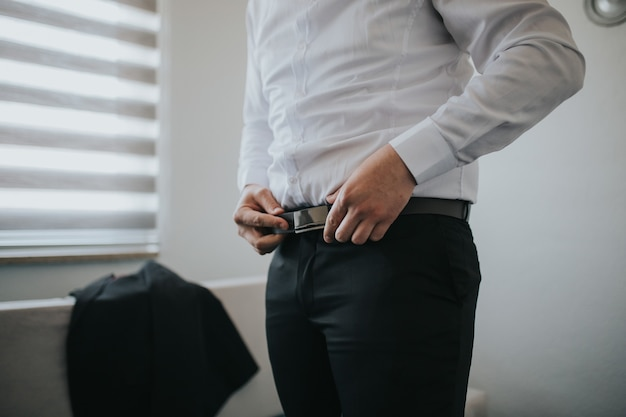 Male is fastening black belt on his trousers