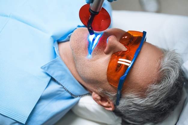 Male is lying in dental chair after being given root canal into tooth in modern clinic