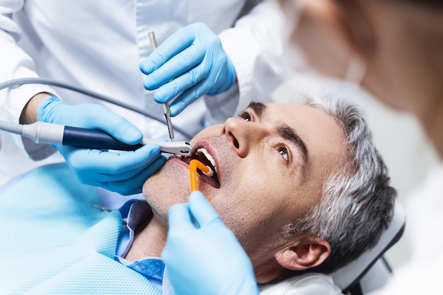 Male is lying in dental chair and being given root canal by dentist and assistant
