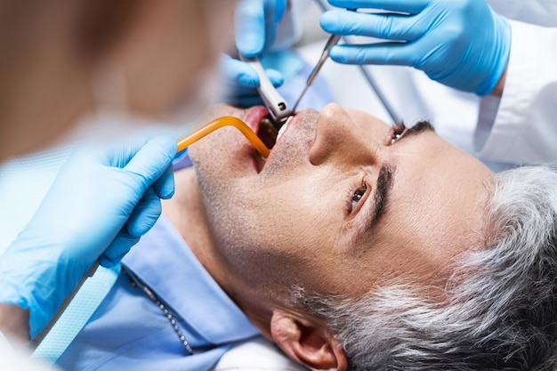 Male is lying in dental chair and being treated by dentist and nurse while being given root canal