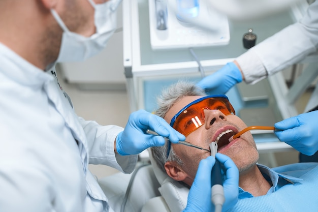 Male is lying in dental chair while dentist and assistant treating him root canal with modern equipment