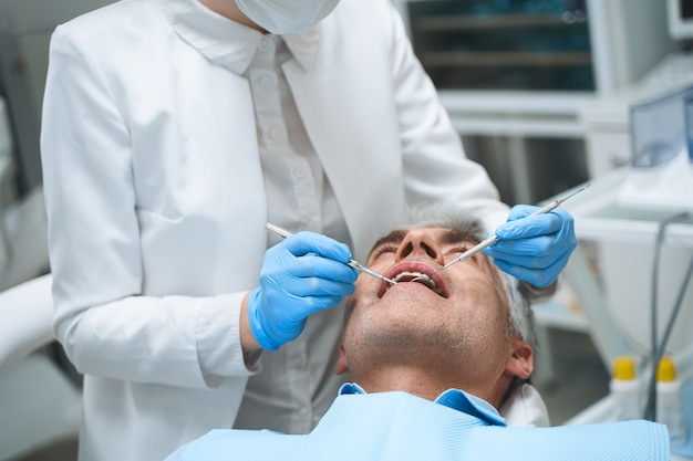 Male is lying in dental chair while specialist is examining him with mirror and explorer