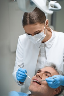 Male is lying in dental chair while woman in sterile mask is helping him solve problems with teeth