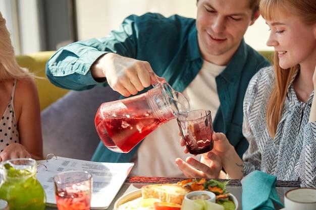 男性は軽いカフェで女性のためにグラスに甘い飲み物を注いでいます
