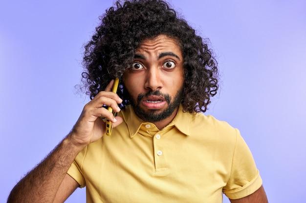 Мужчина грустит из-за ошибки, удивленный мужчина разговаривает по телефону с партнером, в шоке, изолированное фиолетовое пространство