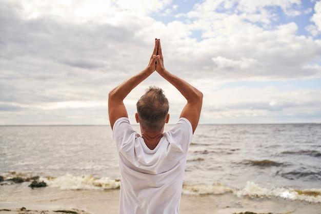 남성은 카메라에 다시 서서 해변에서 하늘에 아사나에 손을 올리고 있습니다.