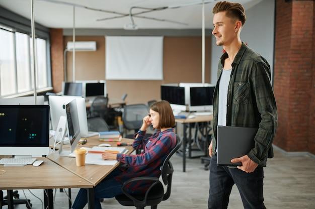 Ит-специалист мужского пола держит ноутбук в офисе. веб-программист или дизайнер на рабочем месте, творческое занятие. современные информационные технологии, корпоративный коллектив