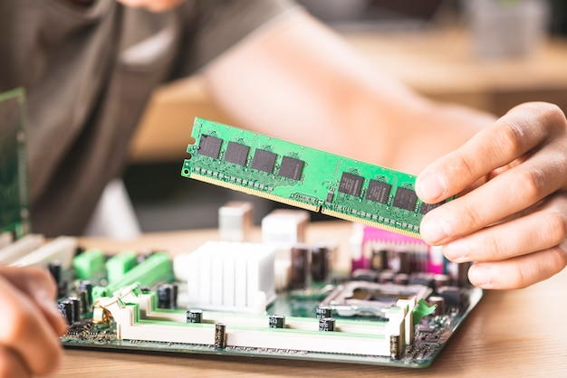 Male it technician installing ram memory in motherboard