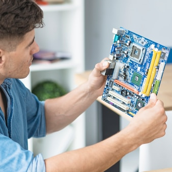 Male it technician looking at pc motherboard