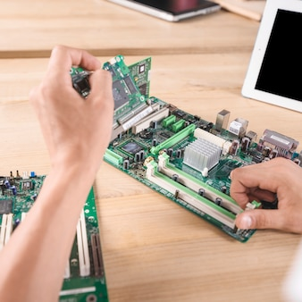 Male it technician repairing electronic computer mainboard on wooden table