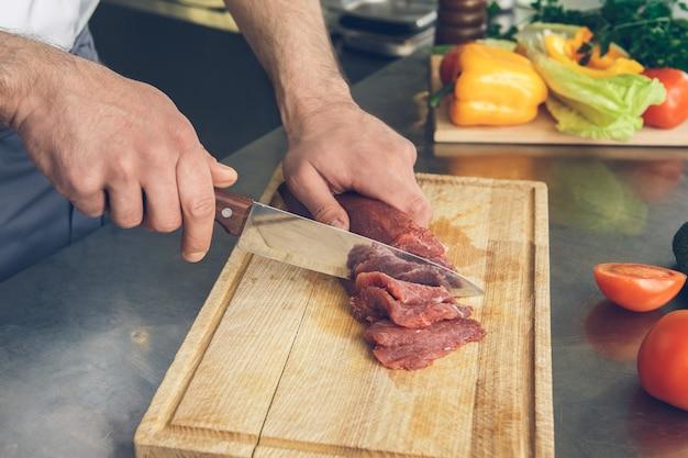 食材を切るキッチンで料理をする男性の日本食レストランのシェフ