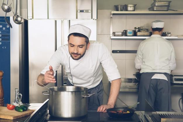 부엌에서 요리하는 남성 일본 레스토랑 요리사는 접시 냄새를 맡는다