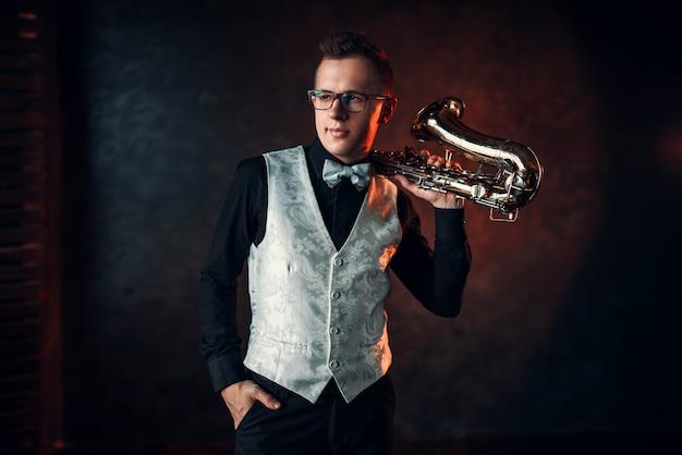 Мужчина джазовый мужчина позирует с саксофоном. джазмен с концепцией саксофона.