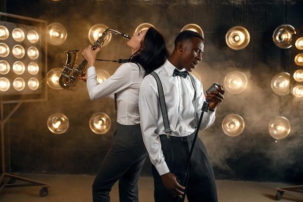男性のジャズ パフォーマーと女性のサックス奏者がサックスを持ち、スポット ライトを当ててステージで演奏します。現場で演奏するジャズプレイヤー