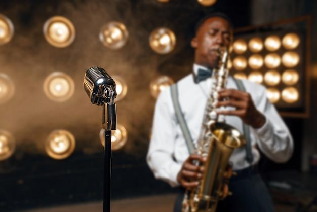 Мужской джазовый исполнитель играет на саксофоне на сцене