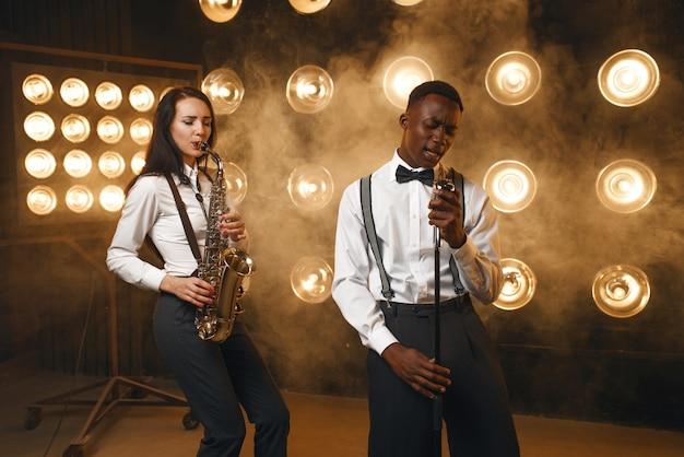 男性のジャズマンと女性のサックス奏者が、スポットライトを当てたステージでサックスを持っている。現場で演奏するジャズパフォーマー