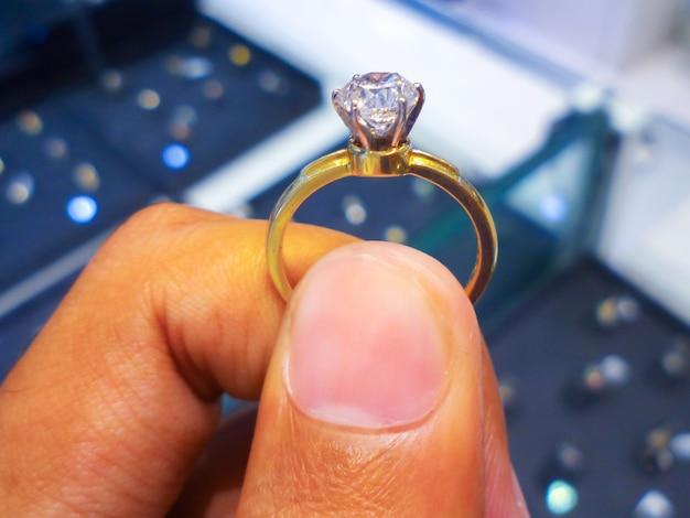 Мужчина-ювелир держит кольцо с бриллиантом, крупным планом