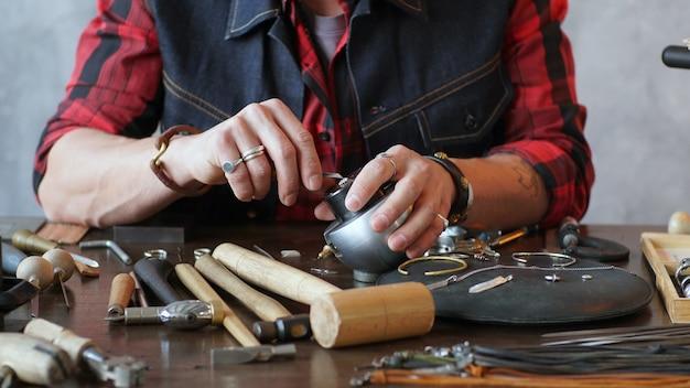 男性の宝石商は、ジュエリーワークショップで彼の職場で働いています。好きな作品