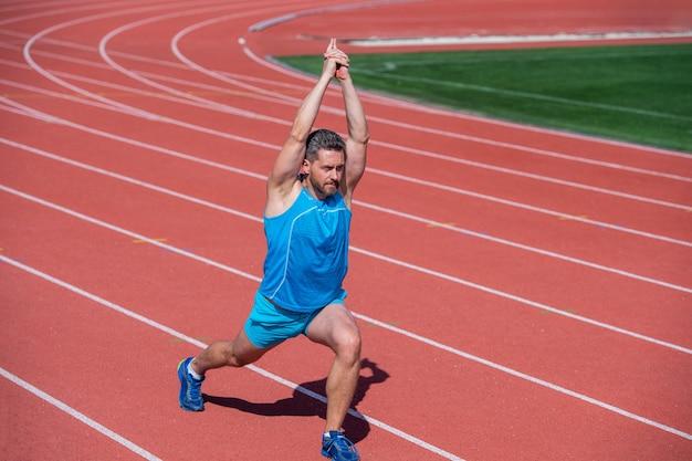 Тренировка спортсмена мужского бегуна и тренировки на открытом воздухе, растяжка.