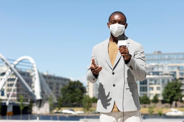 医療用マスクを着用した男性ジャーナリスト