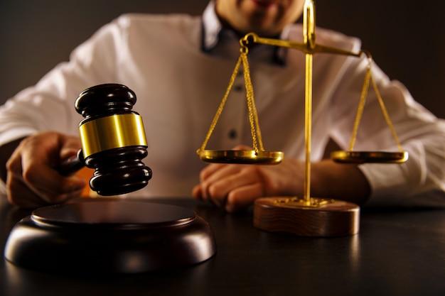 男性裁判官は机の上で木製のガベルを打ちました。弁護士の概念。