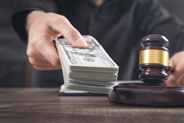 お金を持っている男性裁判官と裁判官ガベル。