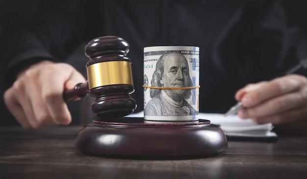 裁判官の小槌とお金を持つ男性裁判官。