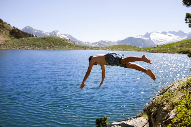 Maschio che salta nel lago con alte montagne rocciose